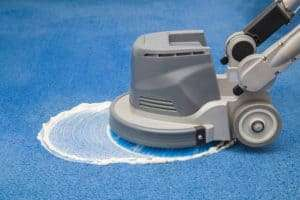 Blue carpet chemical foaming, rubbing and cleaning with professionally disk machine. Early spring regular cleanup. Cleaning service concept.